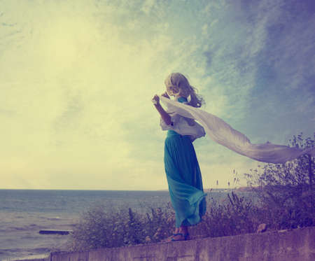 despedida: Foto de la vendimia de Lonely Woman con la bufanda que agita en el mar con foto Tonos Espacio Soledad Concept Foto de archivo