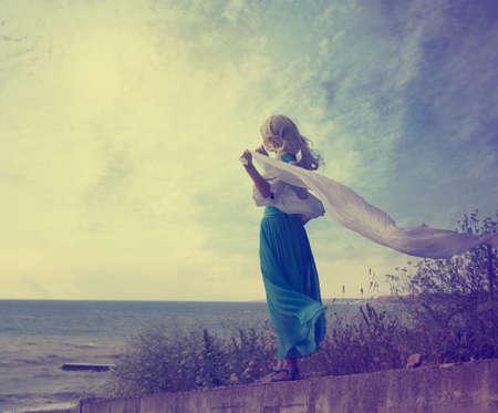 Vintage Foto van Lonely Woman met Zwaaien sjaal op de zee Getinte Foto met Copy Space Solitude Concept