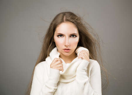Winter Portrait of Trendy Woman in White Cashmere Sweater with Blowing Hair on Gray Background Stock Photo