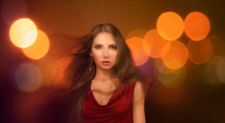 windy city: Portrait of a Beautiful Young Woman in Fashionable Red Dress over Night City Lights  Nightlife Concept  Toned Photo