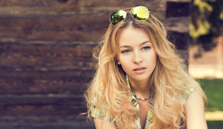 Portrait of Beautiful Blonde Woman on Wooden Wall  photo