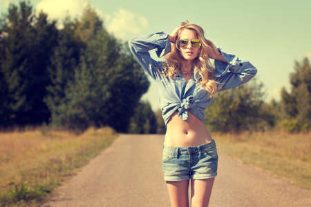Portrait of Sexy Blonde Woman with Hands behind her Head Walking on Country Road  Toned Photo  Street Style