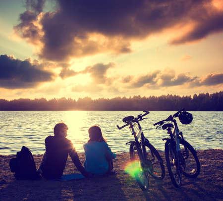 일몰에서 휴식 자전거와 로맨틱 커플. 여름 자연 배경입니다. 활동적인 레저 개념입니다. 톤의 사진.
