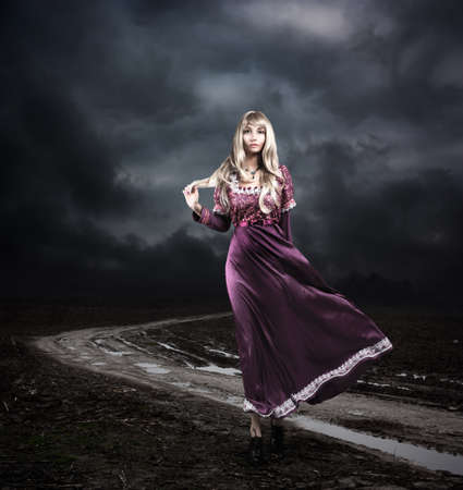 Full Length Portrait of Fantasy Woman in Waving Purple Dress Walking on Dirty Road. Moody Sky. HDR Cloudscape.