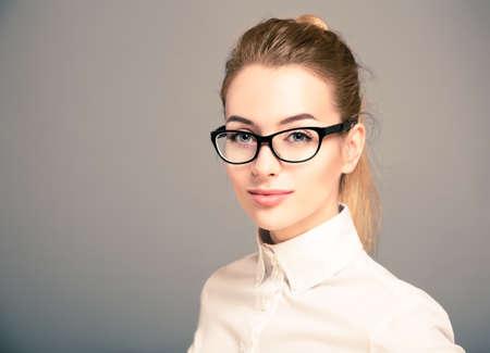 Portret van mooie zakelijke vrouw draagt een wit shirt en bril Stockfoto