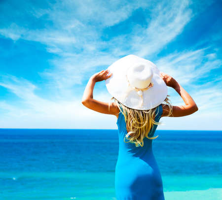 Blonde Woman in Blue Dress Standing at Sea and Holding White Hat  Rear View  Summer Vacation Concept  Standard-Bild
