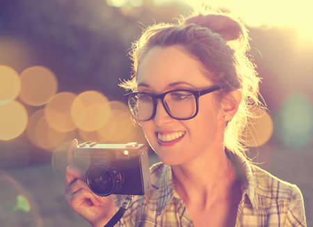Happy Smiling Hipster Girl in Glasses Taking a Photo with Vintage Camera  Toned Photo with Bokeh  Modern Youth Lifestyle Concept