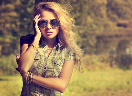 Trendy Hipster Girl in Sunglasses Touching Her Face. Summer Modern Youth Lifestyle. Toned Photo. Stock Photo