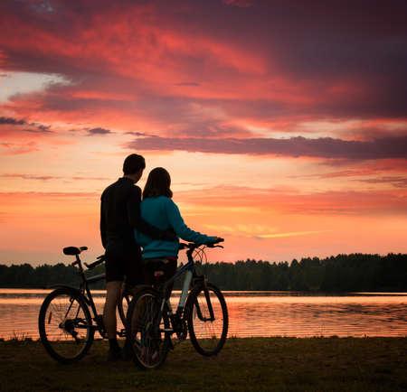 silueta ciclista: Pareja romántica con Bicicletas Observación de la puesta del sol. Fondo del verano con la naturaleza Hermosas nubes, el cielo y el río. Concepto de ocio activo.