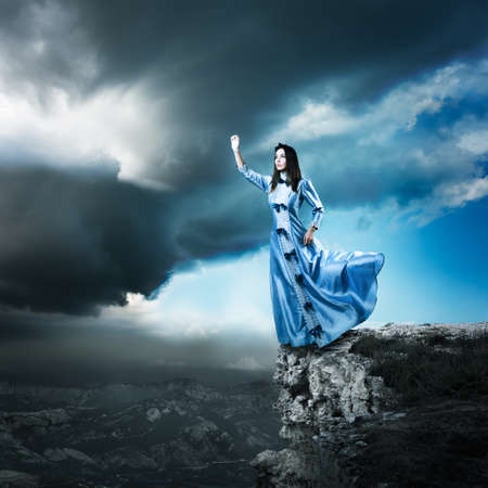 the historical: Full Length Photo of Fantasy Woman in Waving Blue Dress Reaching for the Light. Dramatic Moody Sky. HDR Cloudscape.
