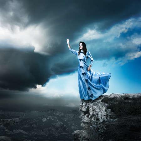 Ganzkörperfoto von Fantasy-Frau im blauen Kleid Winken Erreichen für das Licht. Dramatische Moody Himmel. HDR Wolkengebilde.