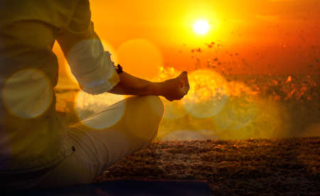 일몰에서 바다로 요가를 연습하는 여자. 황금 bokeh와 아름다운 톤의 사진. 건강한 라이프 스타일 개념입니다. 스톡 콘텐츠