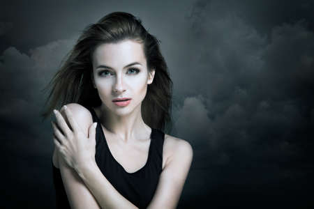 Lonely Woman on the Background of Dark Moody Sky. Sadness Concept. Stock Photo