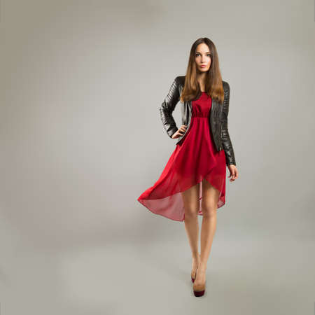 Full Length Portrait of a Woman in Red Chiffon Dress on Gray Backgound Stock Photo