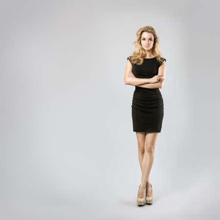 리틀 블랙 드레스에 섹시한 금발의 여자의 전체 길이 초상화는 팔과 몸 자세 신체 언어 개념을 폐쇄 다리를 교차