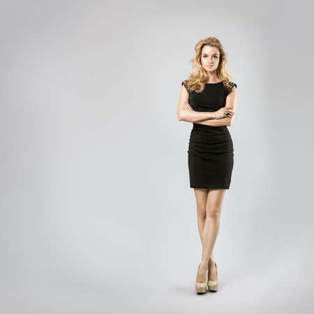 Full Length Portrait of a Sexy Blonde Woman in Little Black Dress  Crossed Arms and Legs  Closed Body Posture  Body Language Concept  Banque d'images
