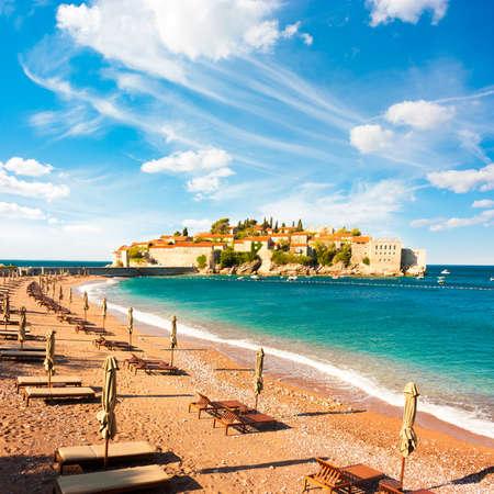 Insel Sveti Stefan in Montenegro, Balkan, Adria. Strand-Stühle auf Seashore. Europäische Luxus Summer Resort. Mittelmeer-Reisen-Konzept. Kopieren Sie Raum.