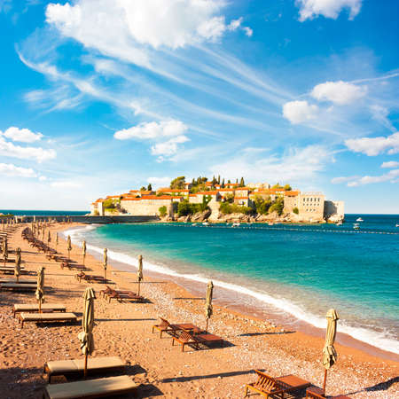 montenegro: Sveti Stefan Island in Montenegro, Balkans, Adriatic Sea. Beach Chairs at Seashore. European Luxury Summer Resort. Mediterranean Travel Concept. Copy Space. Stock Photo