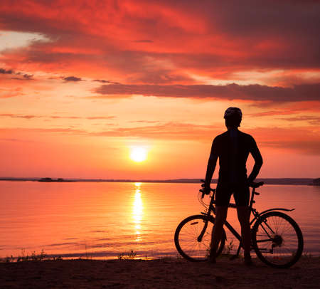 Rear View of a Young Man Standing with a Bicycle at Sunset. Healthy Lifestyle Concept. Copyspace. photo