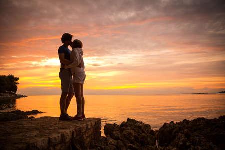 novios besandose: Pareja rom�ntica abraz�ndose y bes�ndose en el mar de fondo Sunset Summer Naturaleza Copia Espacio Love Relationship Concept Foto de archivo