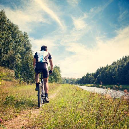 自然背景健康的なライフ スタイルのコンセプトに自転車に乗って若者の背面図