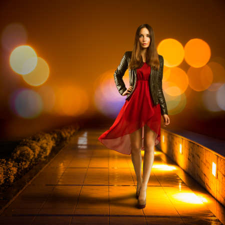 Full Length Portrait of a Woman in Red Chiffon Dress Walking in Night City  Modern Nighlife Concept  Bokeh Background  Copy Space  photo