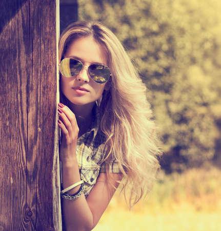 サングラス夏の現代若者のライフ スタイルにおける流行のヒップスター女の子トーンの写真