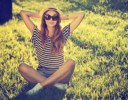 sitting pretty: Trendy Hipster Girl Relaxing on the Grass  Toned and Filtered Photo  Modern Youth Lifestyle Concept