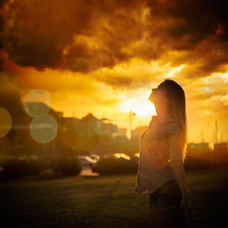 Silhouette of Young Woman at Urban Sunset. Dramatic Sky.    Stock Photo