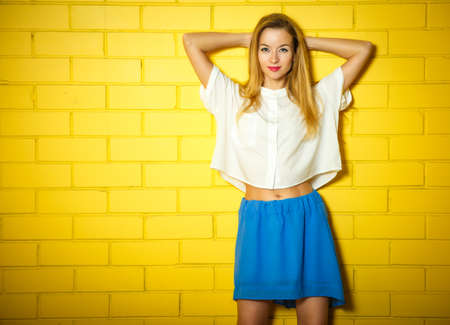 Portrait of Trendy Hipster Girl with Hands behind Head on Yellow Brick Wall Background. Urban Fashion Concept. Copy Space.