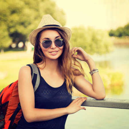 Trendy Hipster Girl Relaxing in the Park. Toned and  Styled Photo. Modern Youth Lifestyle Concept.