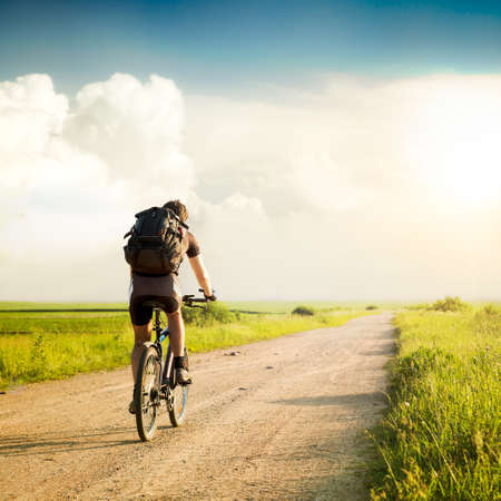 Rear View of a Man with Backpack Riding a Bicycle on Beautiful Nature Background. Healthy Lifestyle and Travel Concept.  Styled Toned Photo. Copyspace. 스톡 콘텐츠
