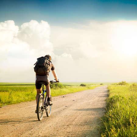 배낭은 아름다운 자연 배경에 자전거를 타고와 남자의 후면보기. 건강한 라이프 스타일과 여행 개념. 톤 사진 스타일. Copyspace입니다. 스톡 콘텐츠