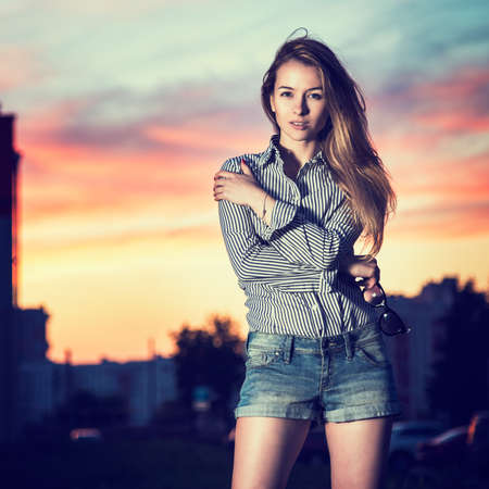 night shirt: Portrait of Beautiful Girl in Evening City Embracing Herself. Urban Fashion Concept. Copy Space. Stock Photo