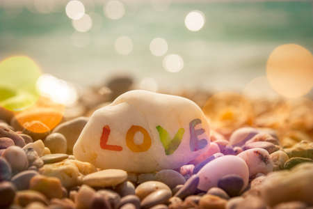 Stone with LOVE text on Sea Background. Filtered Photo with Bokeh. Romantic Travel Concept.