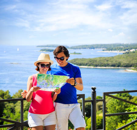 Happy Couple Looking at the Map. Summer Sea Background with Islands. Copy Space. Travel and Vacation Concept.