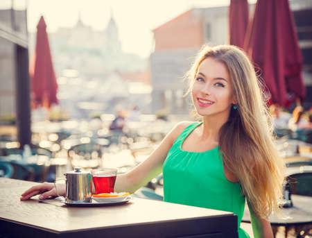 카페 야외에서 차를 마시는 젊은 여자. 여름 도시 배경입니다. 필드의 얕은 깊이. 톤의 사진. 스톡 콘텐츠