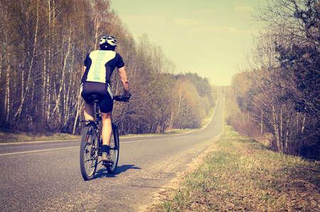 bicicleta: Vista trasera de un hombre deportivo que monta una bicicleta en la carretera nacional. Estilo de vida saludable concepto. Foto virada.