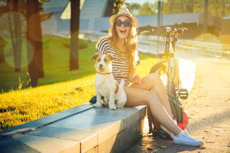 lifestyle: Glückliche Hippie-Mädchen mit ihrem Hund und Fahrrad in der Stadt. Toned und Filtered Foto. Moderne Youth Lifestyle-Konzept.