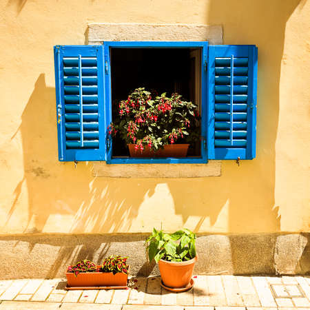 Retro Blue Window with Open Shutters in Mediterranean Style with Flowers in Pot.