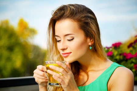 Mujer joven que bebe té verde al aire libre. Fondo de verano. Poca profundidad de campo. Foto de archivo