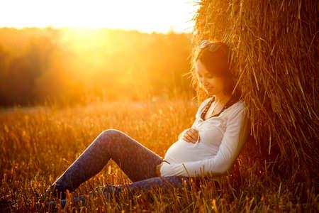 젊은 임신 한 여자 일몰 건초 더미에 앉아 그녀의 아랫 배를 포용. 7 월 임신. 출산 개념. 톤의 사진. 스톡 콘텐츠