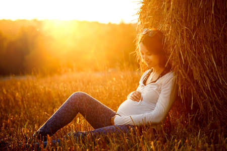Young Pregnant Woman Sitting by the Haystack at Sunset and Embracing her Belly. 7 Month Pregnancy. Maternity Concept. Toned Photo. Archivio Fotografico