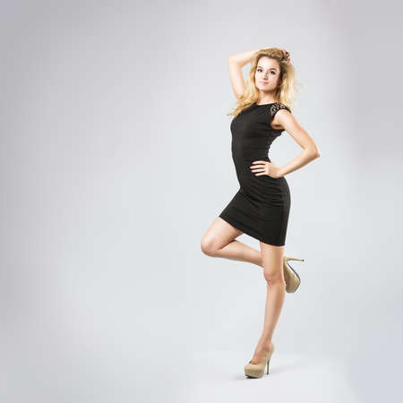 Full Length Portrait of a Sexy Blonde Woman Dancing in Little Black Dress. Fashion and Beauty Concept. Gray Background. Standard-Bild