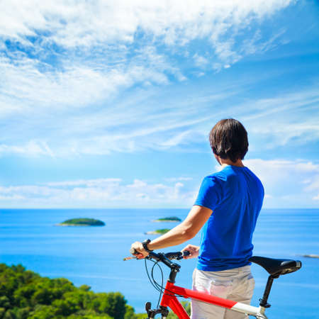 Rear View of a Man with a Bicycle on Summer Sea Background. Healthy Lifestyle and Travel Concept. Copy Space. Stock Photo