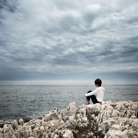 Lonely Woman Sitting at Stormy Sea. Toned and Desaturated Photo with Copy Space. Solitude Concept. Imagens