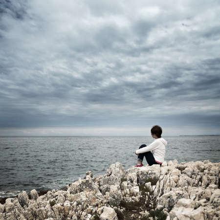 mujeres tristes: Solitaria mujer sentada en el mar tempestuoso. Tonificada y sin saturaci�n de fotos con espacio de copia. Solitario.