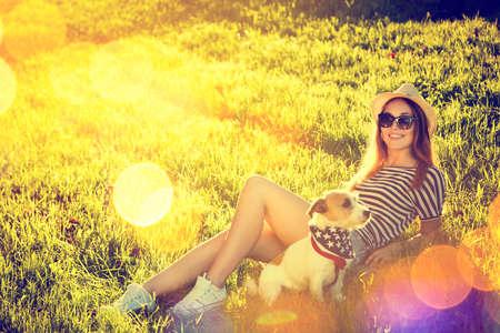 chicas guapas: Chica feliz Hipster con su perro que miente en la hierba. Tono y Filtered fotos. Moderno estilo de vida Concepto de la Juventud.