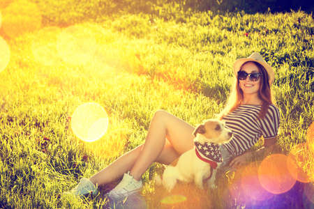 hot girl: Happy Hipster Girl with her Dog Lying on the Grass. Toned and Filtered Photo. Modern Youth Lifestyle Concept.