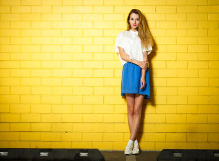 model: Full Length Portrait of Trendy Hipster Girl Standing at the Yellow Brick Wall Background. Urban Fashion Concept. Copy Space.
